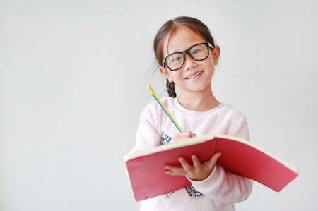 Asian Schoolgirl wearing eyeglasses holding and writes in a notebook with pencil on white background.