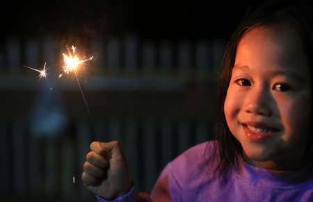 Happy little Asian child girl enjoy playing firecrackers. Banque d'images
