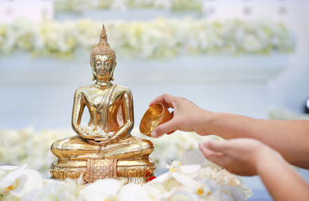 Water blessing ceremony for Songkran Festival or Thai New Year. People paying respects to a statue of Buddha by pouring water onto it.
