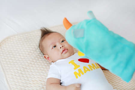 Mother playing animal puppet with her infant baby boy on the bed room at home.