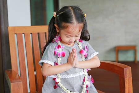 "Little Girl Thailand's Respect ""Sawatdee"" sitting on the wooden chair."
