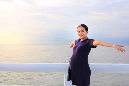 Happy pregnant Asian woman with open arms standing on seashore at sunset.