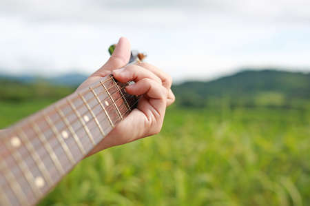 Hand playing on acoustic guitar in the nature. 免版税图像