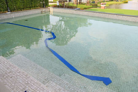 Swimming pool under maintenance with blue rubber hoses immersed. Change new water.