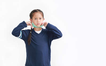Asian little kid girl wearing medical face mask slung on her chin isolated on white background. Amid covid-19 pandemic concept