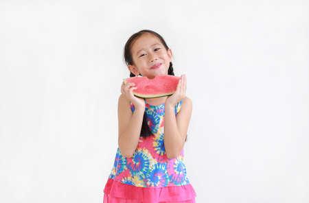 Happy asian little child girl eating watermelon isolated on white background Standard-Bild