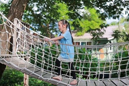Asian little child girl playing on suspension wooden bridge. Kid walking on rope bridge Equipment at park playground. Zdjęcie Seryjne