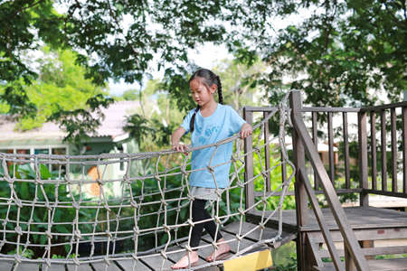 Asian little child girl playing on suspension wooden bridge. Kid walking on rope bridge Equipment at park playground. 免版税图像