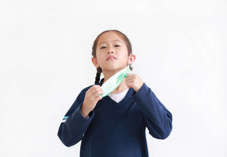 Asian little child girl with wearing medical mask isolated on white background. Focus at medical mask and his hands.