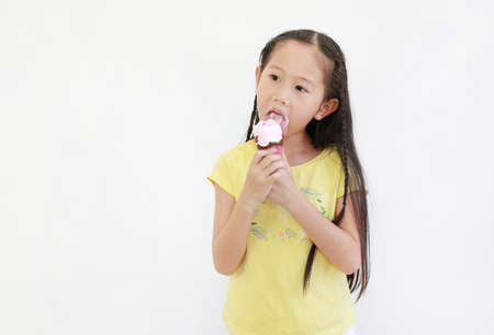 Portrait asian little child girl eating ice cream cone isolated on white background. Archivio Fotografico