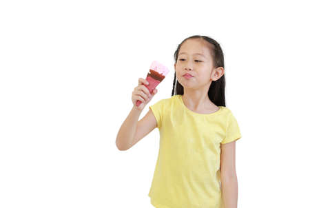 Portrait asian little child girl eating ice cream cone isolated on white background. 版權商用圖片