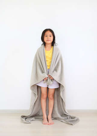 Asian little kid girl standing covered shoulder with soft gray blanket indoor. Winter season concept Archivio Fotografico