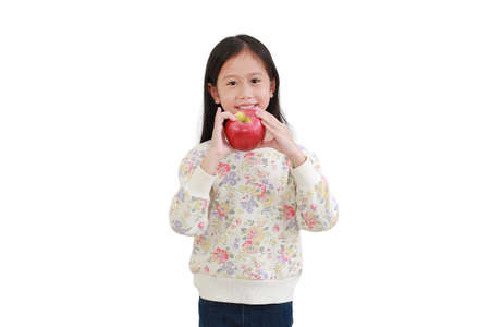 Little asian girl eating red apple over white background Archivio Fotografico