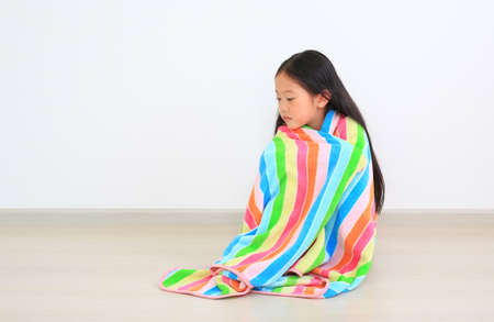 Asian little childd girl sitting wrapped covered in soft multicolor blanket and looking down in the room