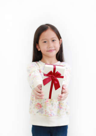 Little asian child girl give you a gift box on white background. Happy new year and Merry christmas concept. Focus at Gift box