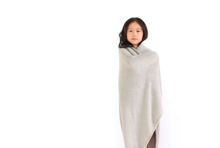 Asian cute little child girl standing wrapped covered in soft gray blanket isolated over white background