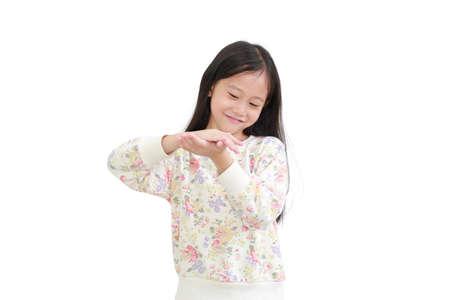 Little asian girl applying lotion in hands over white background 版權商用圖片