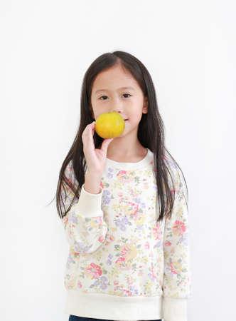 Portrait of little asian kid girl holding orange fruit on white background 版權商用圖片