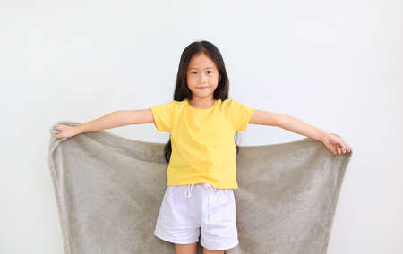 Asian little kid girl spread arms with gray blanket isolated on white background. winter season concept