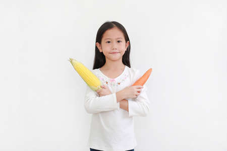 Little asian girl holding carrot and sweet corn gesture cross one arm standing isolated on white background. Kid and vegetable concept