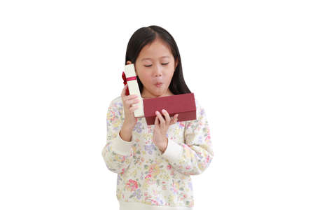 Excited little asian kid girl while open gift box on white background. Happy new year and Merry christmas concept