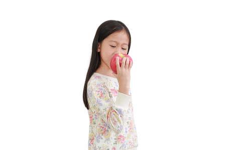 Little asian kid girl bite red apple isolated over white background