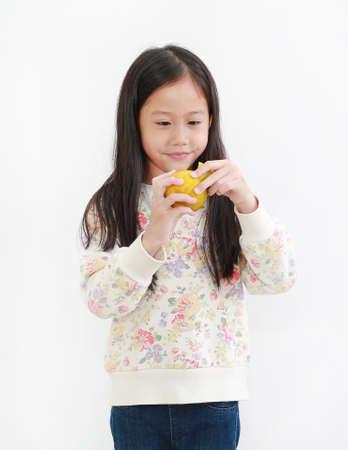Portrait of little asian girl peeling orange on white background