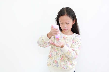 Little asian girl pouring talcum powder on hand over white background 版權商用圖片