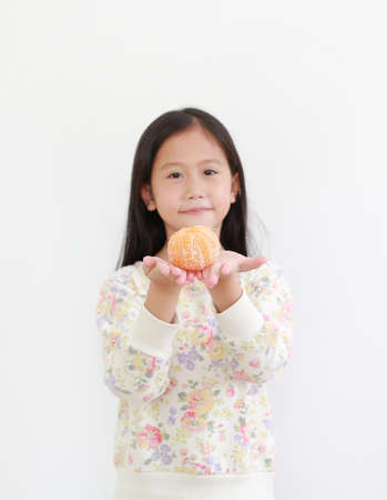 Asian little child girl holding peeled orange fruit on white background. Focus at orange in hands