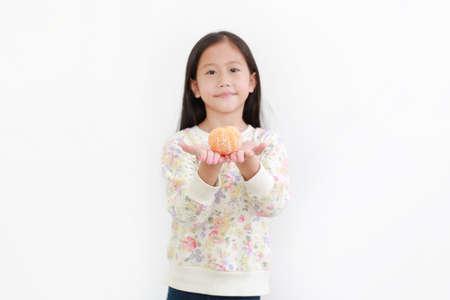Portrait of little asian girl holding peeled orange fruit on white background. Focus at orange in hands