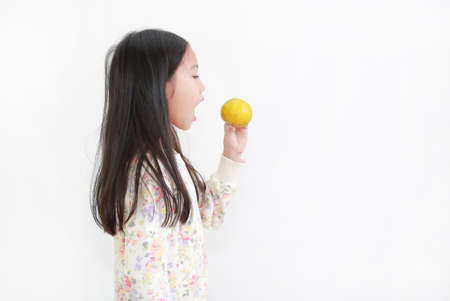 Portrait little asian kid girl holding not peeled orange fruit and gesture eating over white background Archivio Fotografico