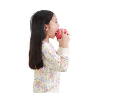 Little asian girl eating red apple over white background. Side view