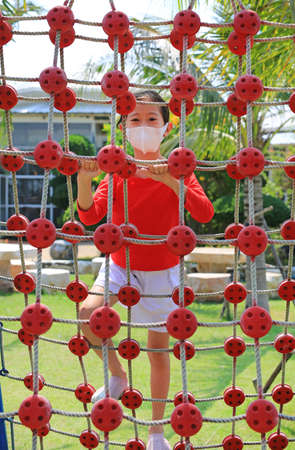 Portrait of asian little child girl wearing a protective mask while playing on climbing rope net.