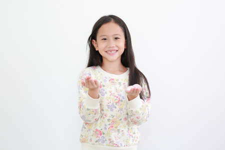 Cheerful asian little girl with lotion cream in hands on white background. Archivio Fotografico