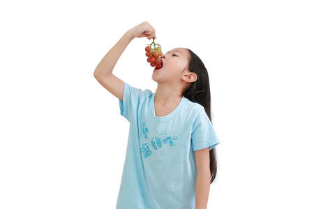 Little asian girl eating purple grape on white background. Kid holding bunch of grapes in the mouth