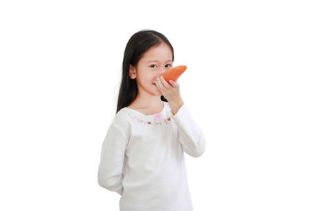 Cute little asian child girl making long nose with carrot isolated on white background