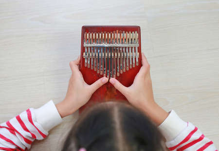 young hands playing Kalimba (Mbira or thumb piano) lying on wood floor at home. African musical instrument.