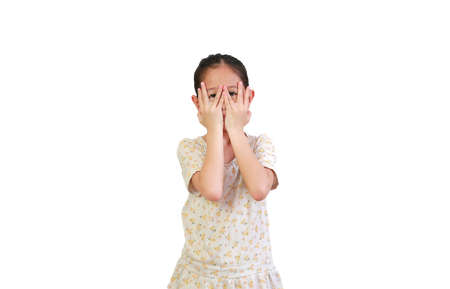 Portrait little asian girl covering eyes while watching through gap in fingers isolated on white background with clipping path. Kid peeking by her hands