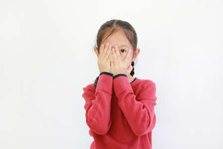 Portrait little asian girl covering eyes while watching through gap in fingers isolated on white background. Kid peeking by her hands Stock fotó