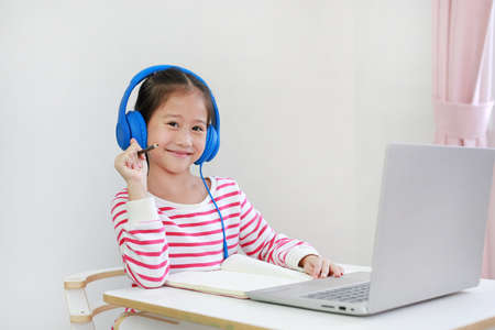Portrait of Asian little child wearing headphone with holding pencil looking at camera study online learning class with laptop computer during new normal Covid-19 coronavirus at home