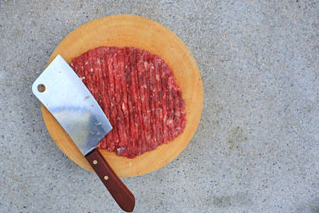 Chopped fine beef with cleaver knife on circle wood cutting board on stone background with copy space. Raw minced meat on wooden block