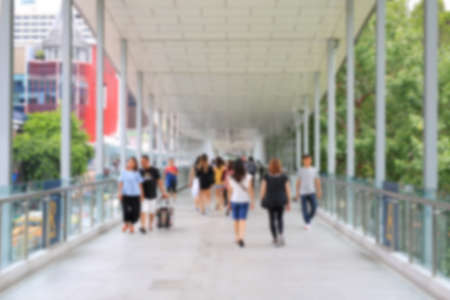 Blurry of people walking on skywalk in bangkok city.