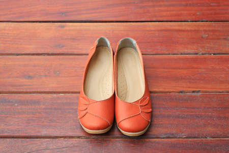 Orange leather female shoes on wood
