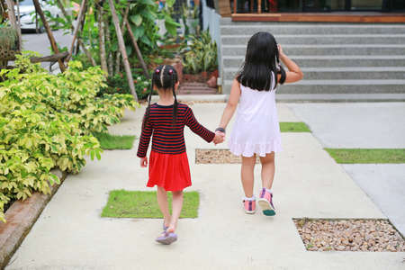 Rear view of Sister hold hands with small children walking on the road garden.