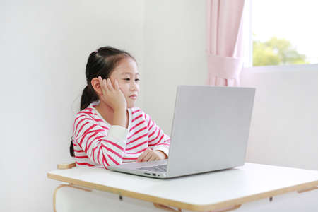 Happy little asian child girl sitting at desk and using laptop computer stay at home