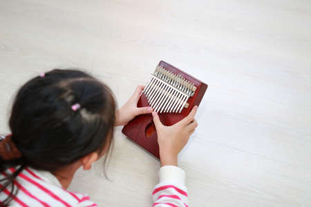 Close-up Asian young hands playing Kalimba (Mbira or thumb piano) lying on wood floor at home. Rear view