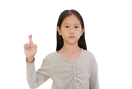 Portrait of Asian little child girl holding fingers crossed isolated on white background with clipping path