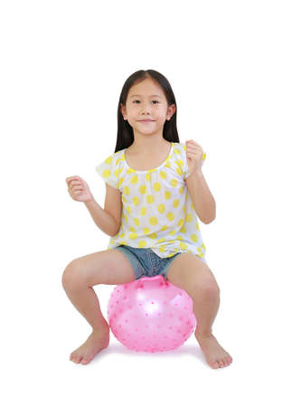 Cute Asian little child playing ride and sitting on round silicone inflatable pink knobby ball isolated on white background with clipping path Stock Photo