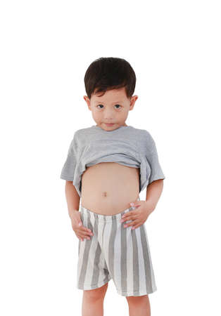 Portrait of Asian baby boy age about 3 years old lifting his shirt show exposing his big tummy isolated on white background with clipping path