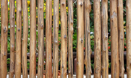 Fence made of small wood logs. Wood texture background.